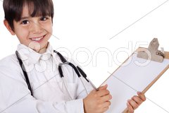 Little boy doctor writes on his clipboard for diagnosis Stock Photos