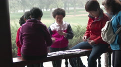 Chinese women play cards in a Beijing park as part of their morning recreation. Arkistovideo