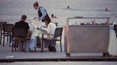 4K couple at restaurant by the sea getting service Stock Footage