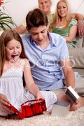 Kids opening christmas gifts with parents in the background Stock Photos