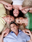 Happy family of four lying on the carpet Stock Photos
