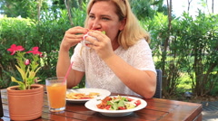 Blonde woman at the restaurant eating salad and hamburger 3 Stock Footage