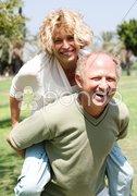 Senior man giving piggy ride to her wife Stock Photos