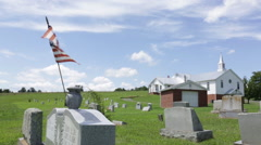 American flag on a headstone in front of a church Stock Footage