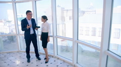 Colleagues discuss project on tablet in clean bright office near panoramic Stock Footage