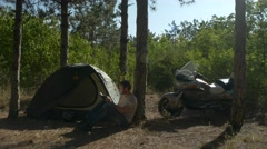 Motorcyclist sitting near tent in woods and writing a book at vacation near camp Stock Footage