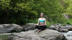 Young and Beautiful Girl is Meditating on the Rock. She Breathes Deeply the Stock Footage