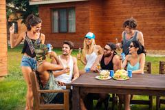 Happy people celebrating and having party at the table outdoors Stock Photos