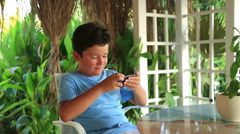 Child relaxing with smartphone in summer cafe 4 Stock Footage