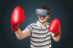Young man is playing video game and is boxing with 3D virtual reality headset Stock Photos