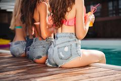 Seductive young women in jeans shorts sitting near swimming pool Stock Photos