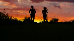 Silhouette of man and woman running  in nature with sunset light Stock Footage