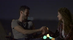 The lovely couple sit on the background of city light. Evening night time Stock Footage