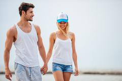Romantic young beautiful couple walking on the beach holding hands Stock Photos