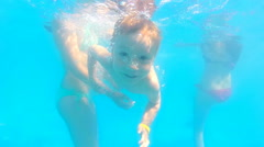 Boy in aqua park swims with open eyes Stock Footage