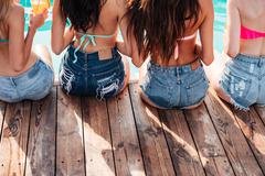 Alluring young women in jeans shorts sitting on wooden terrace Stock Photos