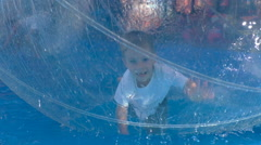 Boy crawling in a large inflatable ball at the amusement park Stock Footage