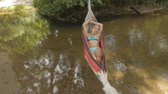 Girl in a bathing suit lying in a hammock over the water Stock Footage