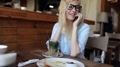 Beautiful Girl Talking on the Phone and Drinking Herbal Tea in a Cafe Stock Footage