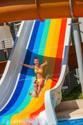 Child on water slide at aquapark show thumb up. Kuvituskuvat