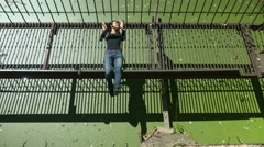 Young beautiful girl lies and laughs on rusty metal bridge over green water. Stock Footage