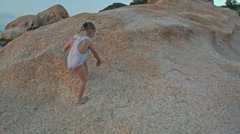 Closeup Little Girl Climbs up Large Bare Rock at Sunset on Beach Stock Footage