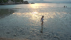 Little Girl Plays in Sea Water against Beach at Sunset Stock Footage