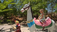 Little Girl Sits on Horse Model on Playground in Temple Park Stock Footage