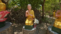 Little Girl Plays at Sitting Buddha Statues in Temple Park Stock Footage