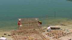 Men Construct Sea Raft with Bamboo Stems on Beach in Vietnam Stock Footage