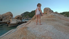 Little Girl Stands on Large Bare Rock Top at Sunset on Beach Stock Footage