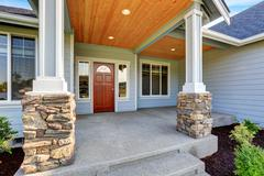 Light blue siding house . Porch with stone base columns and concrete floor. N Stock Photos