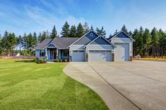 Luxury blue house with curb appeal. Three car garage and long, wide asphalt d Stock Photos