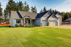 Luxury blue house with curb appeal. Three car garage with driveway . And fres Stock Photos