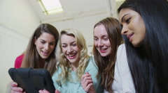 Happy casual group of young female friends relaxing with a tablet computer Stock Footage