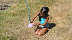 Asian Girl Blows Up A Water Balloon In Summer Stock Footage