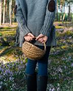 Girl standing back to camera in the forest and holding a basket Stock Photos