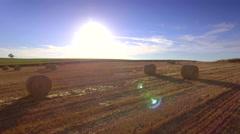 Agricultural rural harvested field haystacks bales horizon sunlight blue sky Stock Footage