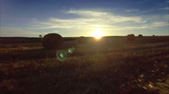 Beautiful aerial drone forward setting sun countryside field hay bales sunset Stock Footage