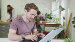 Young male student concentrating as he works within a shared study space Stock Footage