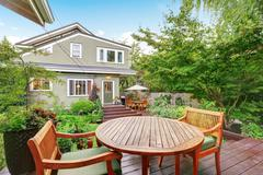 Back deck of guest house with wooden table set. Luxury house exterior. Northw Stock Photos