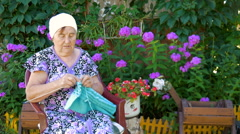 Elderly woman knitting sitting on the street outside his home. Stock Footage
