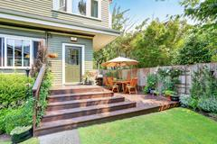 Backyard area with walkout deck, patio table set and well kept lawn. Northwes Stock Photos