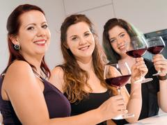 Three women making a toast with wine Stock Photos