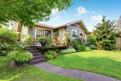 Backyard area with nicely trimmed garden. Wooden deck with stairs and flower  Stock Photos