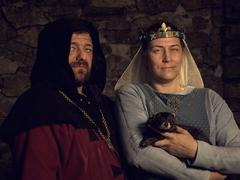 Medieval lovers. Fairy couple with a weasel in  costumes Stock Photos