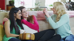 Young girlfriends gossiping together at home with popcorn Stock Footage