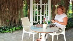 Woman sitting at the summer cafe and using her smartphone 5 Stock Footage