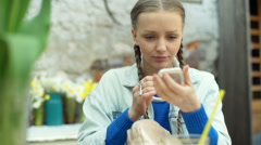 Girl in braids sitting in the outdoor cafe and improving makeup Stock Footage
