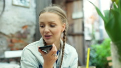 Pretty girls in braids sitting in the outdoor cafe and talking on loudspeaker Stock Footage